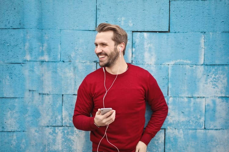 Guy listening to real estate investing podcasts on his iphone app