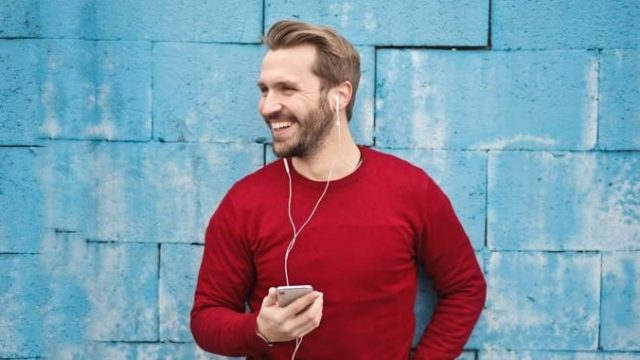 Guy listening to real estate podcast on his iphone app